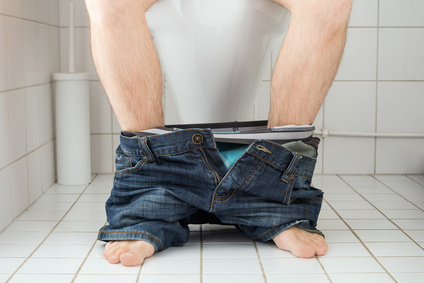 Man sitting on a toilet seat with his pants and boxers down