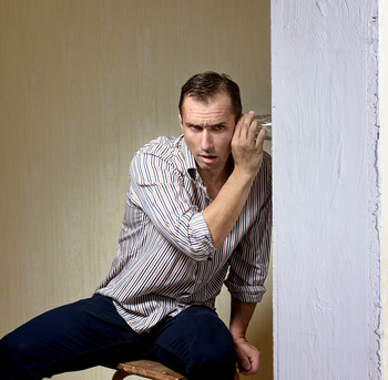 Man with a glass listening to a conversation through the wall